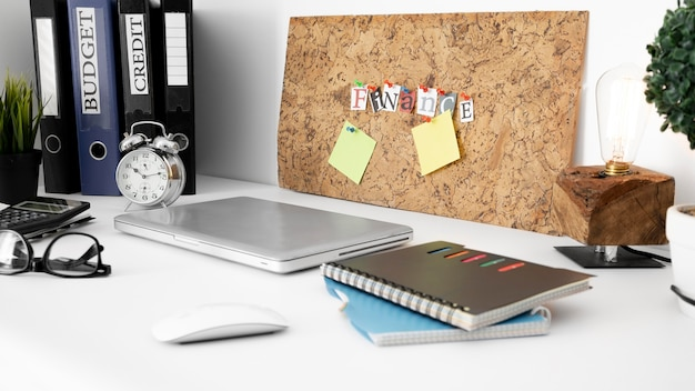 Office desk surface with notebooks and laptop