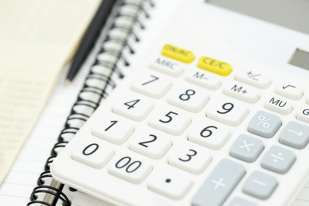 Office desk table calculator with notepad book, bank account and black pen. top view with copy space. investment calculation accounting, financial concept