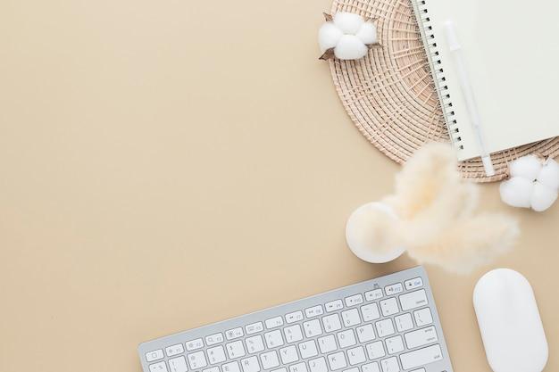 オフィスデスクテーブル上面図。葦草と綿の花のセラミック花瓶、コピースペースのあるベージュのテーブル、ベージュの職場構成、フラットレイ、モックアップ
