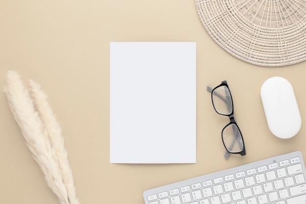 オフィスデスクテーブル上面図。葦草と綿の花のセラミック花瓶、コピースペースとベージュのテーブルの上の白紙、ベージュの職場構成、フラットレイ、モックアップ