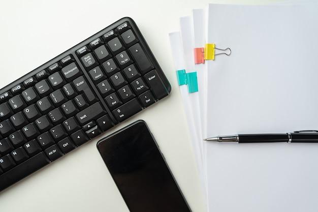 コンピュータのキーボードと消耗品を備えたオフィスデスクテーブル。白い背景に。コピースペースのある上面図。モックアップ