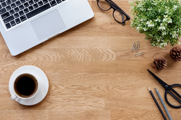 Office desk table with laptop, office supplies and coffee cup