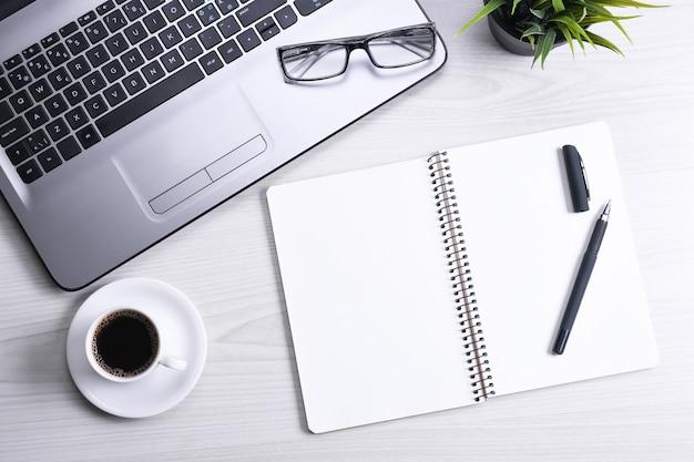 Стол офисный стол с ноутбуком, смартфон, чашка кофе и принадлежности, на деревянных фоне. вид сверху с копией пространства, плоская планировка.