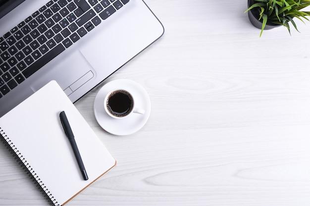 ラップトップ、スマートフォン、一杯のコーヒーと消耗品、木製の背景の上のオフィスの机のテーブル。コピースペース、フラットレイの上面図。