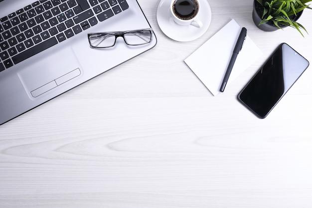 ラップトップ、スマートフォン、一杯のコーヒーと消耗品、木製のオフィスデスクテーブル。コピースペース、フラットレイの上面図。