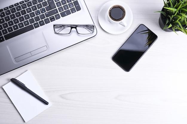 Стол офисный стол с ноутбуком, смартфон, чашка кофе и принадлежности, на деревянном