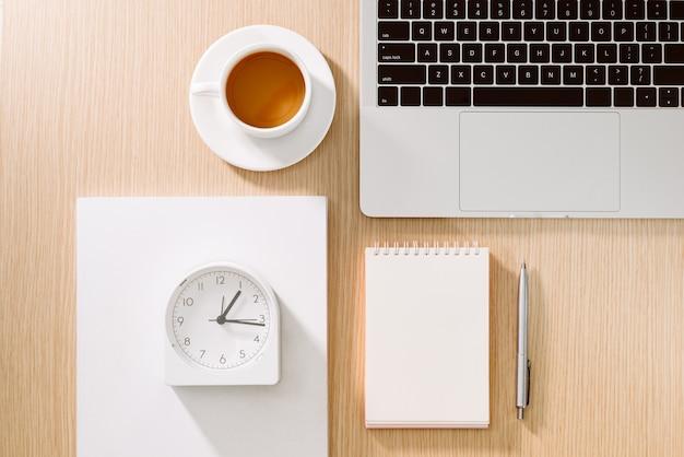 Стол офисный стол с ноутбуком, смартфон, чашка кофе, ручка, карандаш и блокнот. канцелярские товары и гаджеты на письменном столе. концепция стола рабочий стол.
