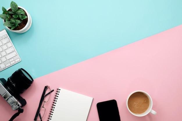 ノート、キーボード、ペン、コーヒーと花のオフィスデスクテーブル。コピースペースのトップビュー。
