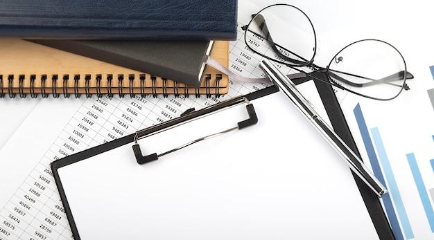白い背景の上のノートブック、消耗品、分析チャートとオフィスデスクテーブル。コピースペースのある上面図