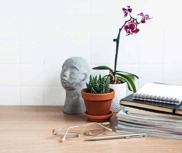 ノートブック、消耗品、観葉植物を備えたオフィスデスクテーブル