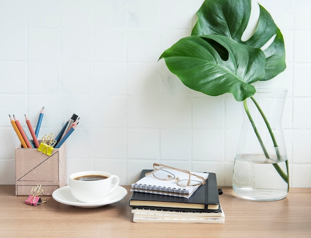Office desk table with  notebooks, supplies and coffee cup.