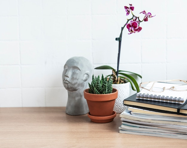 Office desk table with  notebooks, supplies and houseplants