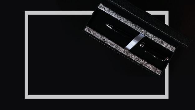 ペン付きオフィスデスクテーブル。コピースペースの上面図-黒い表面のビジネスコンセプト