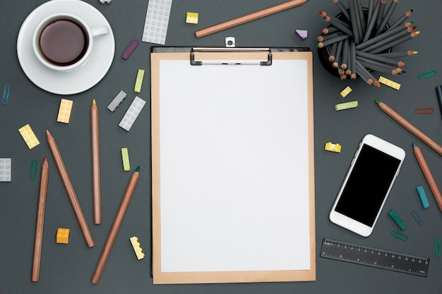 鉛筆、消耗品、電話、カップ付きのオフィスデスクテーブル