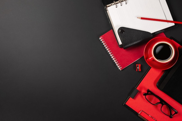 Office desk table with red cup of coffee and notebooks. top view with copy space.