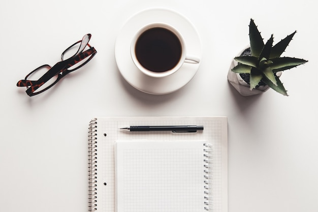 Стол офисный стол с принадлежностями, чашкой кофе и цветком. вид сверху с копией пространства