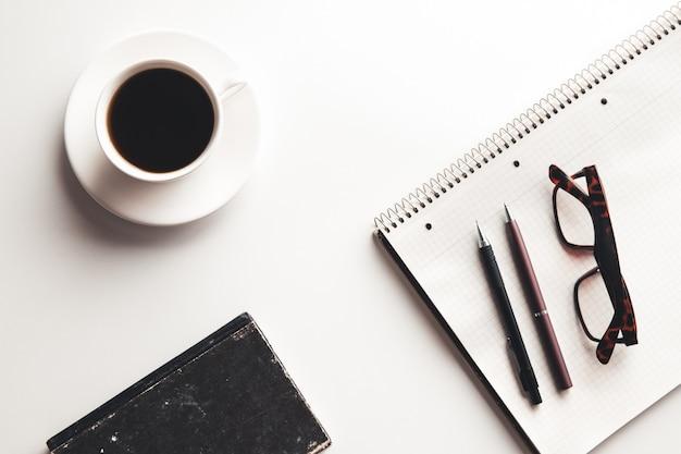 사무용 책상 테이블에는 용품, 커피 컵, 꽃이 있습니다. 복사 공간이 있는 상위 뷰