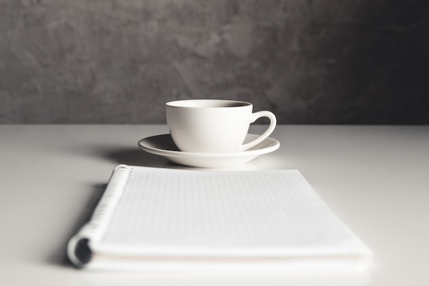 消耗品、コーヒーカップ、花のオフィスデスクテーブル。コピースペースのある上面図