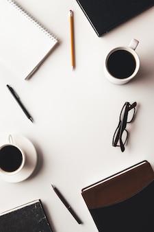 消耗品、コーヒーカップ、花のオフィスデスクテーブル。上面図