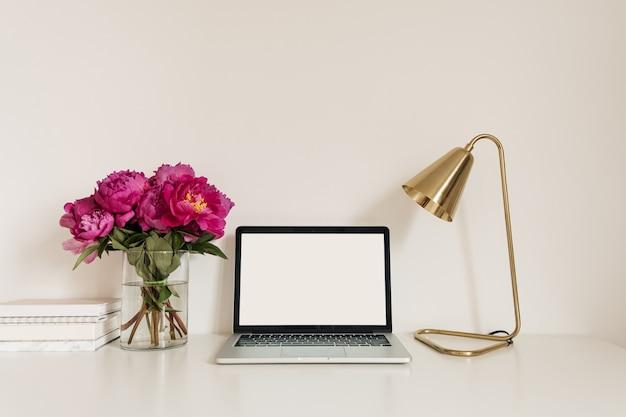 빈 복사본 공간 노트북 화면 사무실 책상 테이블 작업 영역. 분홍색 모란 꽃 부케와 현대적인 세련된 홈 인테리어 디자인