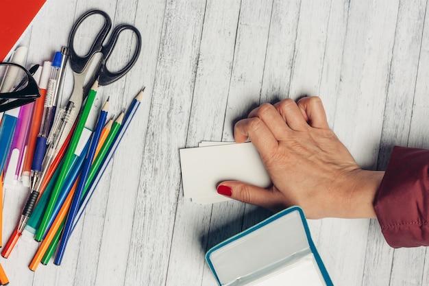 사무실 책상 평가 및 여성 손 문구 연필 가위 마커