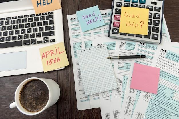 オフィスデスク、納税申告書付きの休憩コーヒーカップの時間。事務処理