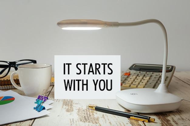 Офисный стол с лампой, которая подсвечивает надпись начинается с вас