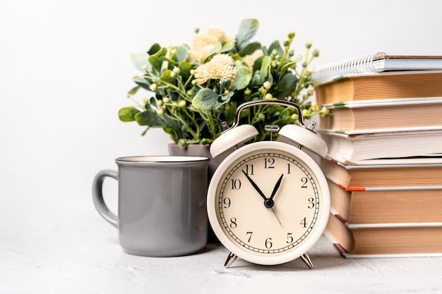 目覚まし時計と本と緑の植物のスタックを備えたオフィスデスク。仕事のコンセプトタイム