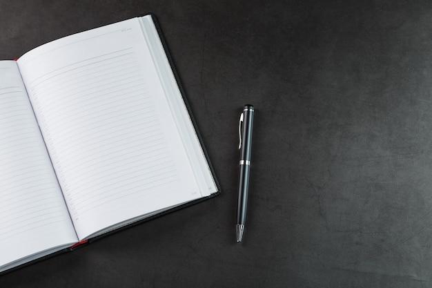 黒の背景に黒のメモ帳とペンでオフィスデスク。コピースペースのある上面図。ビジネスの目標と目的の概念