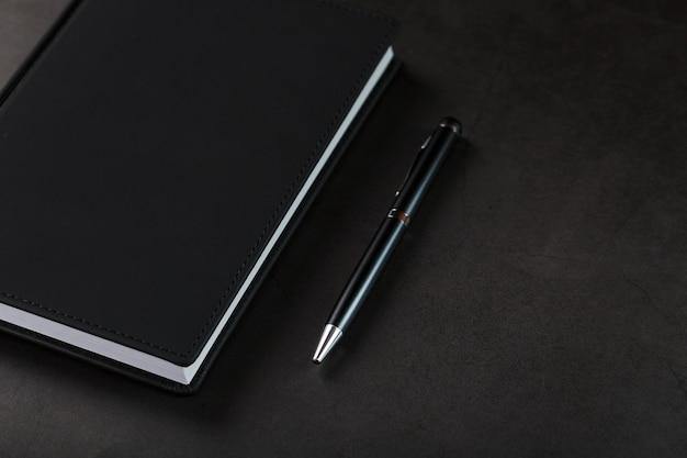 Офисный стол с черным блокнотом и ручкой на черном фоне. вид сверху с копией пространства. концепция бизнес-целей и задач