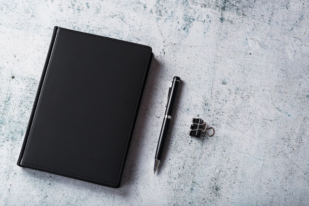 검은 메모장 및 회색 배경에 펜 사무실 책상. 복사 공간이있는 상위 뷰. 비즈니스 목표 및 목표 개념