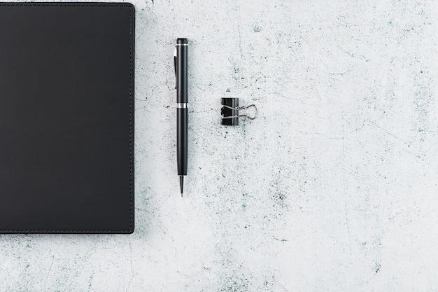 灰色のテーブルに黒いメモ帳とペンが付いたオフィスデスク。コピースペースのある上面図。ビジネスの目標と目的の概念