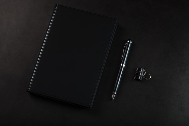 Office desk with black notepad and pen on black background. top view with copy space. business goals and objectives concept