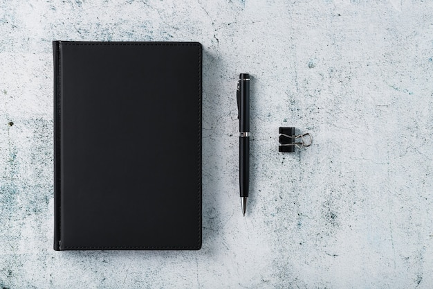 Office desk with black notepad and pen on gray background. top view with copy space. business goals and objectives concept