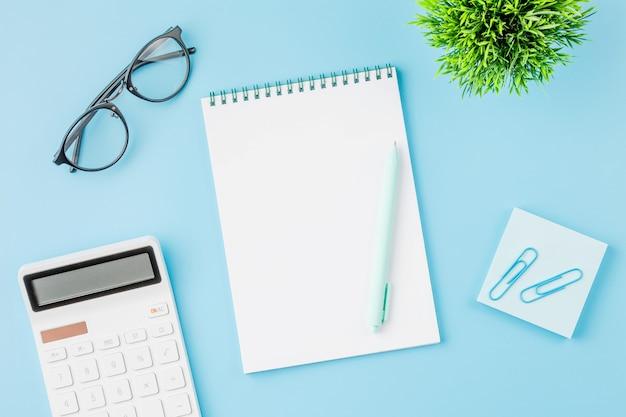 電卓のメモ帳とメガネ付きのオフィスデスク