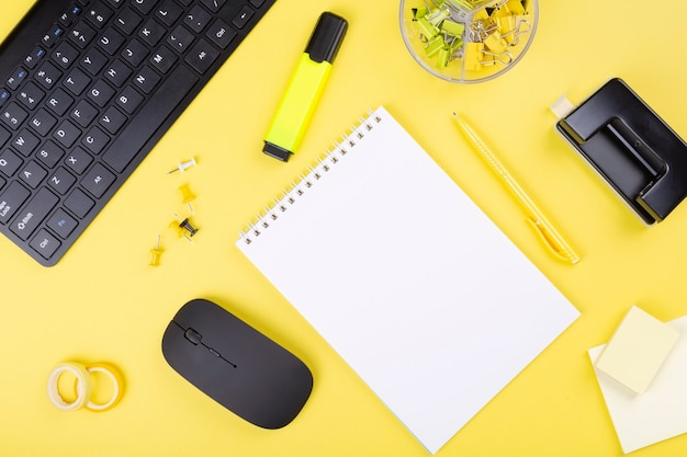 Office desk with computer and stationery, yellow background.