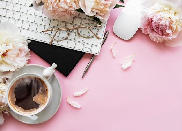 一杯のコーヒーと牡丹の花のオフィスデスク