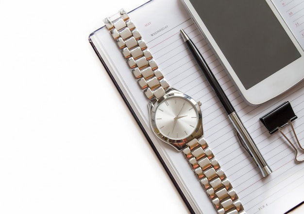 Office desk with a diary, smartphone, pen on a notepad, men's wrist watch. top view