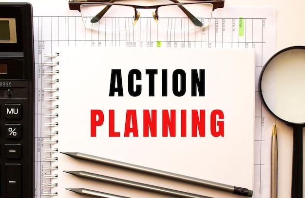 재정 서류, 돋보기, 계산기, 안경 사무실 책상. action planning 텍스트가있는 메모장 페이지