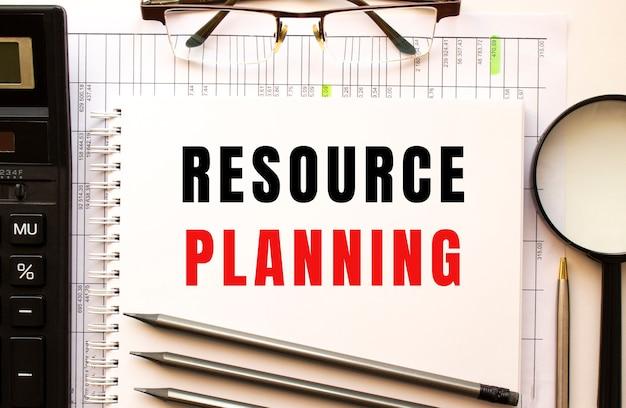 재정 서류, 돋보기, 계산기, 안경 사무실 책상. resource planning 텍스트가있는 메모장 페이지