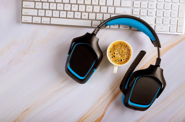 Office desk with headset call center manager desktop on cup of coffee top view