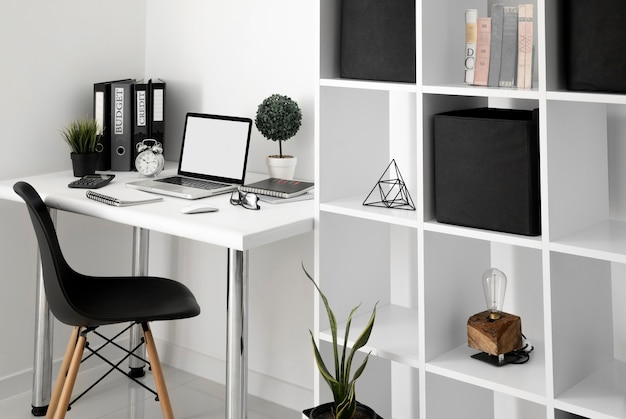Office desk with laptop and chair next to shelf