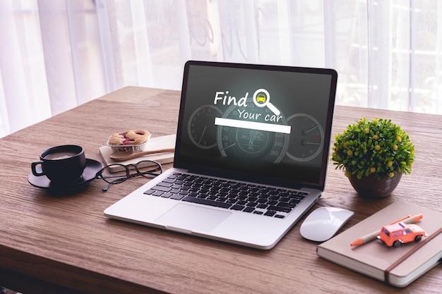 ノートパソコンと事務机。画面上の車のウェブサイト、車をオンラインで購入するという概念を見つける