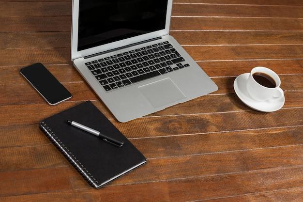 Письменный стол с ноутбуком, блокнот и чашка кофе