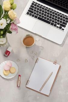 ラップトップ付きのオフィスデスク、ピンクのトルコギキョウの花束、コーヒーマグ、白地に日記