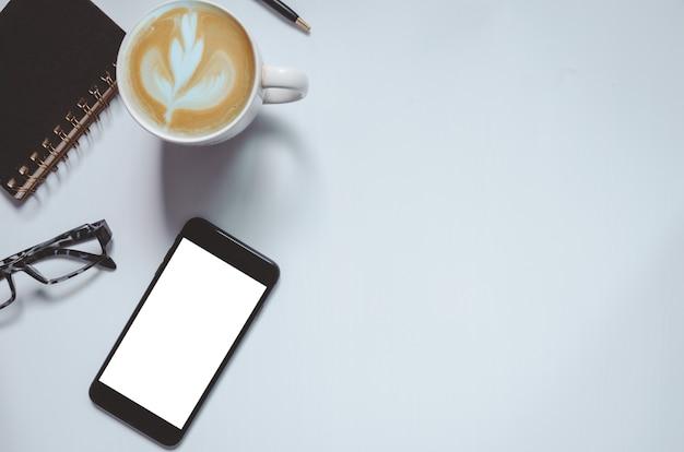 회색 빈티지 톤 배경에 스마트 폰, 펜, 커피 및 노트북을 모의하는 사무실 책상