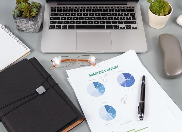 보고서 및 노트북 및 커피 컵 근처 현대 가제트와 함께 사무실 책상을 닫습니다.