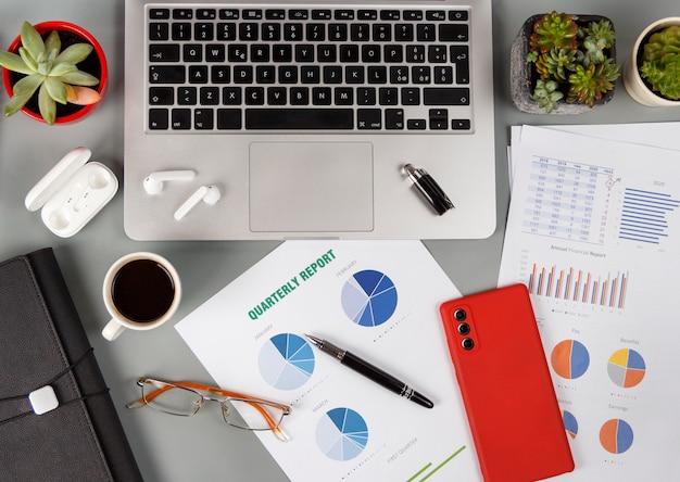 ノートパソコンとコーヒーカップの上面図の近くにレポートとモダンなガジェットを備えたオフィスデスク