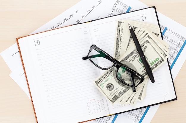 レポート、空白のメモ帳、現金を備えたオフィスデスク。コピースペースで上から見る