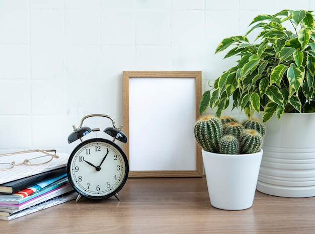 Office desk with stack of notepads, alarm clock, office supplies and house plants